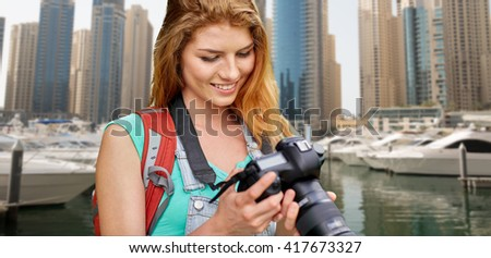 adventure, travel, tourism, hike and people concept - happy young woman with backpack and camera photographing over dubai city and harbor with boats background - stock photo