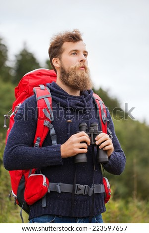 adventure, travel, tourism, hike and people concept - man with red backpack and binocular outdoors - stock photo