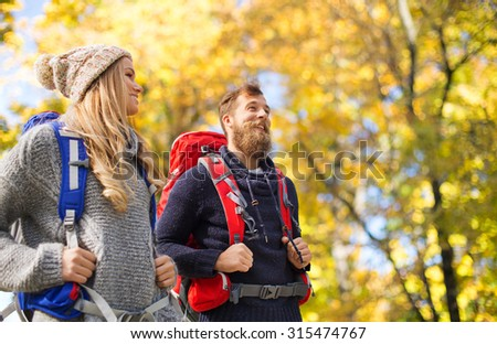 adventure, travel, tourism, hike and people concept - smiling couple walking with backpacks over autumn natural background - stock photo