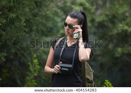 adventure, travel, tourism, hike and people concept -  young woman with backpack and camera photographing outdoors - stock photo