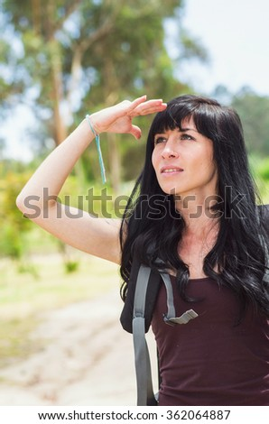 Adventurous brunette in hiking environment, walking away from camera looking back, forest background. - stock photo