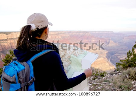 Adventurous female at the Grand Canyon holding a map - stock photo