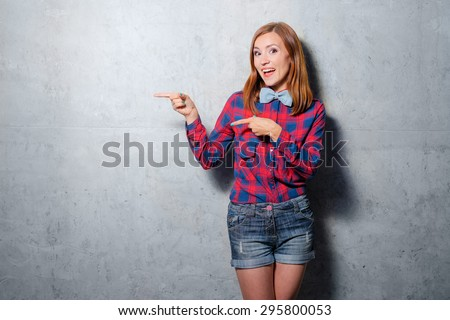 Advertise your product. Attractive young woman in plaid shirt pointing copy space against wall. - stock photo