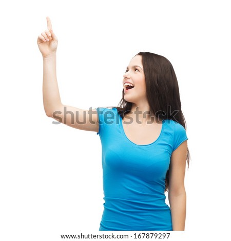 advertisement concept - attractive teenager in casual clothes pointing her finger up - stock photo
