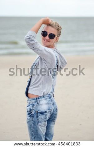 advertisement, summer holidays, travel and people concept - happy smiling young attractive girl in jeans and glasses posing on the beach on a background of the sea. Smile and happy face.  - stock photo