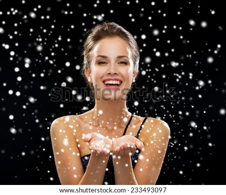 advertisement, winter holidays, christmas, people and luxury concept - laughing woman in evening dress holding something imaginary over blue snowy background - stock photo
