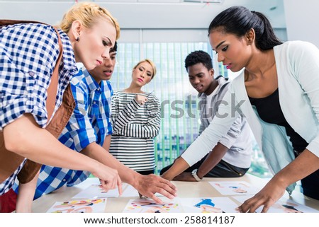 Advertising agency team choosing key visual among pictures spread out on the table - stock photo