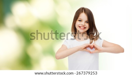 advertising, childhood, ecology, charity and people - smiling little girl in white t-shirt making heart-shape gesture over green background - stock photo
