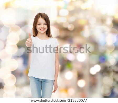 advertising, childhood, gesture, holidays and people - smiling girl in white t-shirt showing thumbs up gesture over sparkling background - stock photo