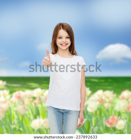 advertising, childhood, nature, gesture and people concept - smiling girl in white t-shirt showing thumbs up over flower field background - stock photo