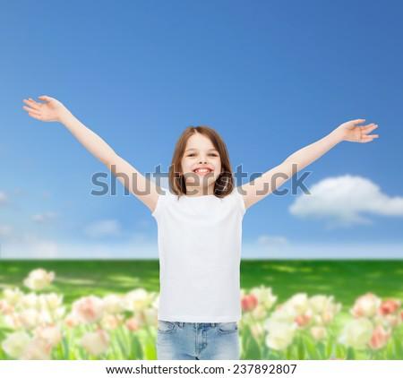 advertising, childhood, nature, gesture and people concept - smiling girl in white t-shirt with stretched out arms over field background - stock photo