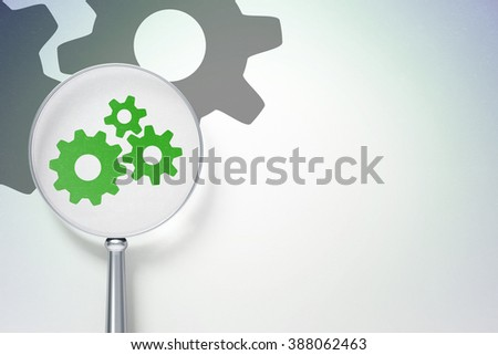 Advertising concept:  Gears with optical glass on digital background - stock photo