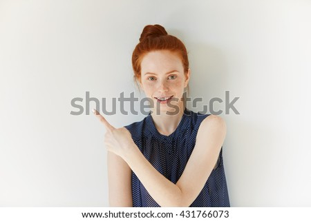 Advertising concept. Happy young woman with red hair and freckles wearing spotted dress, standing against white concrete wall background with copy space for your information or promotional content - stock photo