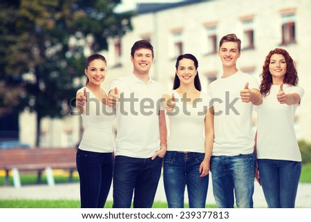 advertising, friendship, education, school and people concept - group of smiling teenagers in white blank t-shirts showing thumbs up over campus background - stock photo