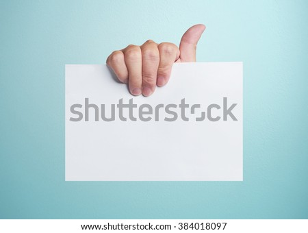 Advertising: Hand holding white empty paper . - stock photo