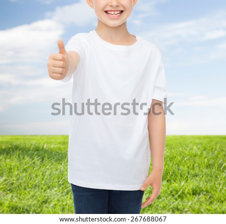 advertising, people and childhood concept - close up of smiling little boy in white blank t-shirt showing thumbs up over blue sky and grass background - stock photo
