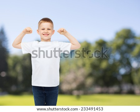 advertising, summer, people and childhood concept - smiling little boy in white blank t-shirt with raised hands over park background - stock photo