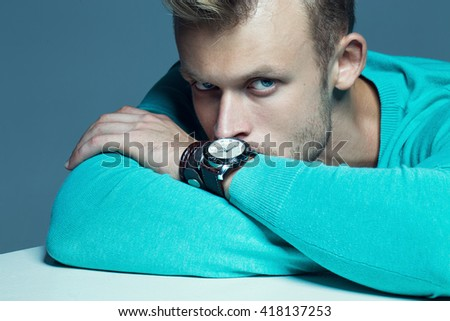 Advertising wrist watch concept. Beautiful (handsome) muscular male model with perfect body in blue jumper and with the clock on his hand. Street style. Black and white, monochrome studio shot - stock photo