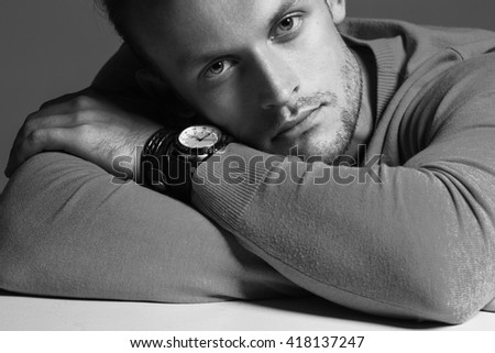 Advertising wrist watch concept. Beautiful (handsome) muscular male model with perfect body in grey jumper and with the clock on his hand. Street style. Black and white, monochrome studio shot - stock photo