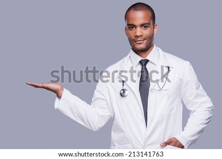 Advertising your product. Confident African doctor holding copy space and looking at camera while standing against grey background - stock photo