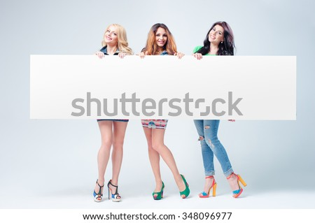 Advertising. Your text here. Gorgeous long hair young women holding an empty board with copy space together. Isolated on white. - stock photo