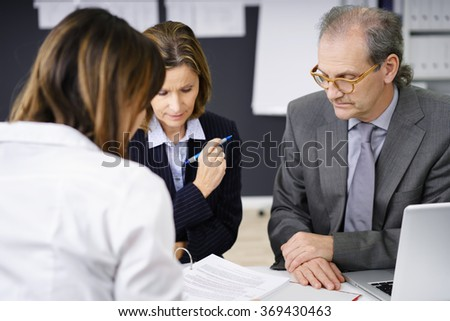 Adviser explaining paperwork to a middle-aged couple at a meeting in her office as they concentrate on the documents - stock photo