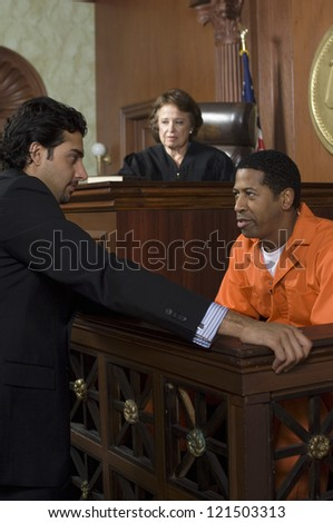 Advocate with defendant and judge sitting in the background - stock photo