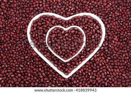 Adzuki bean health food in heart shaped porcelain dishes forming an abstract background. - stock photo