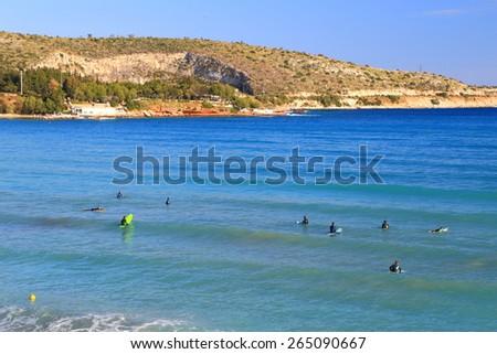 Aegean sea shore and surfers preparing to ride, Vouliagmeni, Greece - stock photo