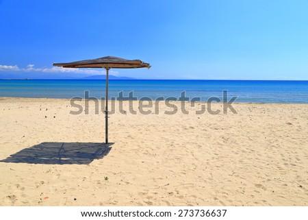 Aegean sea shore near wide beach with small umbrella, Greece - stock photo