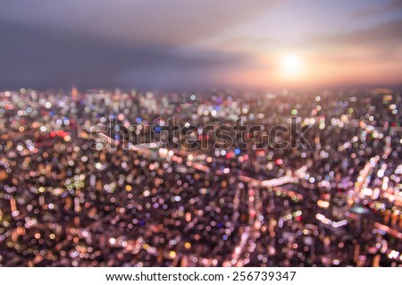Aerial bokeh of Tokyo skyline from above during sunset and blue hour - Japanese world famous capital with spectacular nightscape panorama - Violet marsala filter on blurred defocused night lights - stock photo