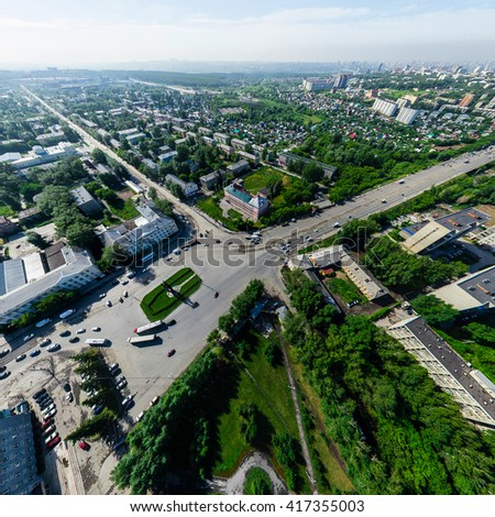Aerial city view with crossroads and roads, houses, buildings, parks and parking lots, bridges. Copter shot. Panoramic image. - stock photo