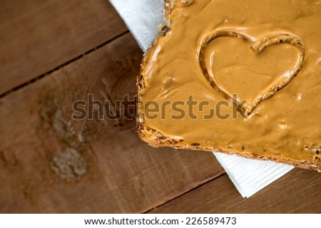 Aerial closeup of peanut butter toast with heart shape on tissue against wood - stock photo