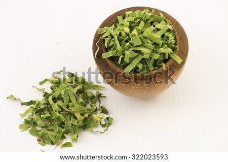 Aerial closeup on shredded pandan leaf in a wooden bowl with some outside the bowl. The leaf is processed to use as herbal tea for its strong sweet fragrance and medicinal benefits.  White background. - stock photo