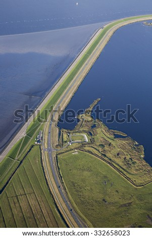 Aerial coastal view of the shore of Ameland Frisian Island with green fields, dike and sea, The Netherlands - stock photo