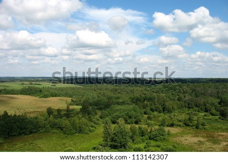Aerial green meadows and forests view on blue sky with clouds background - stock photo