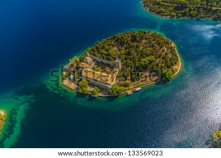 Aerial helicopter shoot of National park on island Mljet, Dubrovnik archipelago, Croatia. The oldest pine forest in Europe preserved and Monastery of Saint Mary on a small island in a big lake. - stock photo