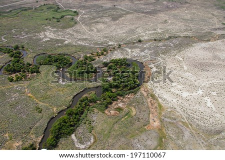 Aerial of a lush green river bed snaking along - stock photo