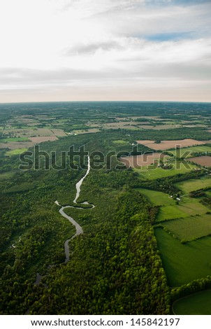 Aerial of a winding river surrounded by forest and agriculture - stock photo