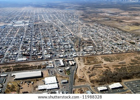 Aerial of border crossing and town of Agua Prieta, with Douglas, Arizona, below on the U.S. side of the border fence. - stock photo