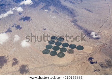 Aerial of green irrigated crop circles in a vast brown expanse of California's Mojave Desert. - stock photo