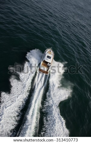 Aerial of luxurious yacht sailing away in the ocean - stock photo