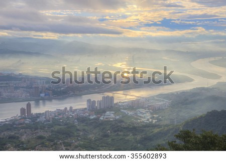 Aerial panorama of foggy Taipei City with a bird's eye view of Kuandu plain, Tamsui River and downtown area at dawn ~ Ethereal scenery of a misty and gloomy morning in Taipei, Taiwan, Asia - stock photo