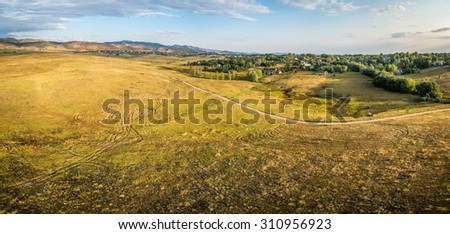 aerial panorama of foothills prairie along Front Range of Rocky Mountains near Fort Collins, Colorado, summer scenery lit by sunrise - - Cathy Fromme Prairie Natural Area with a bike trail - stock photo
