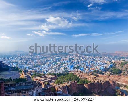 "Aerial panorama of Jodhpur, also known as ""Blue City"" due to the vivid blue-painted Brahmin houses. View from Mehrangarh Fort (part of fortifications is also visible).  Jodphur, Rajasthan, India - stock photo"
