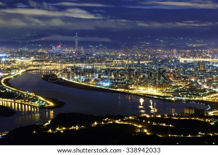 Aerial panorama of Taipei City in a blue gloomy night, with view of Kuandu  plain, Tamsui River, downtown area and Taipei 101 tower in XinYi District, in evening twilight - stock photo
