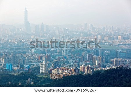 Aerial panorama of Taipei City in morning fog with view of Taipei 101 Tower in downtown area, Keelung River and distant Mountains ~ Scenery of Taipei City under foggy morning sunshine - stock photo