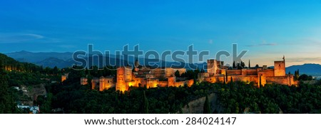 Aerial panoramic night view of Alhambra Palace in Granada, Spain with Sierra Nevada mountains at the background - stock photo