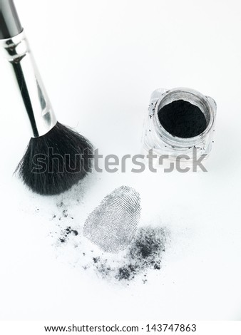 aerial perspective view of a fingerprint revealed by printing dust, with a brush and printing dust recipient - stock photo