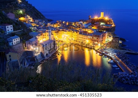 Aerial scenery of beautiful Vernazza at dusk with reflections of lights on peaceful water, an amazing village by the rugged coast in Cinque Terre, Italy - stock photo